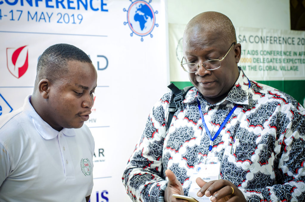 Chris K. Nuatro, Marketing and Partnership Officer in an interacting with a delegate at 13th INTEREST Conference
